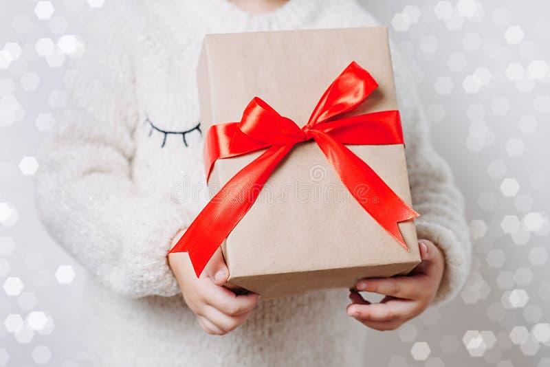 Kind-` s übergibt das Halten der Weihnachtsgeschenkbox mit hellem rotem Bogen Abschluss oben lizenzfreies stockbild