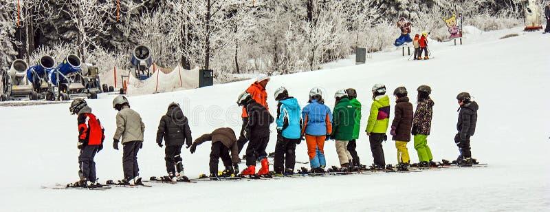 Kind-` s alpine Skischule Lehrer- und Kinderstudenten in der bunten Skiausrüstung stockbild