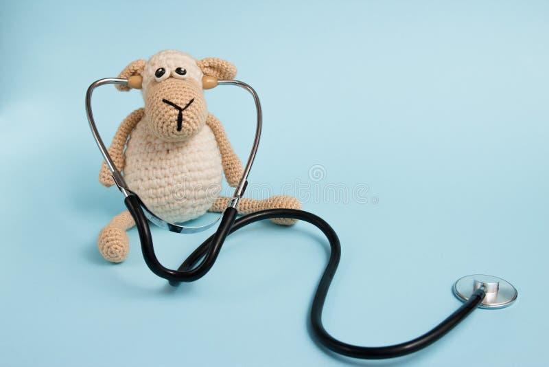 Kind-` s Doktorkonzept Schafspielzeug und -stethoskop auf blauem Hintergrund, Raum für Text lizenzfreies stockfoto
