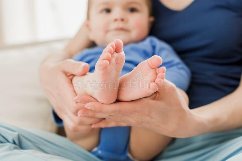 Kind-` s Füße in Mutter ` s Händen Mutter, die ihren Sohn auf Knien hält lizenzfreie stockfotos