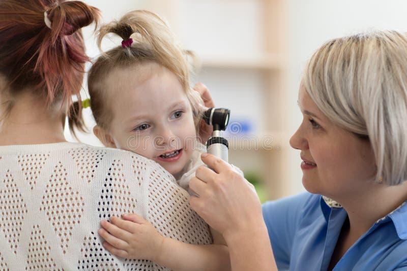 Kind-` s Facharzt für Hals- und Ohrenleiden, der Ohrprüfung des kleinen Mädchens tut stockbilder