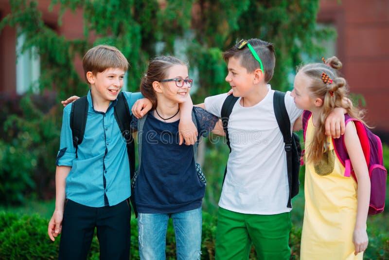 Kind-` s Freundschaft Vier kleine Schüler, zwei Jungen und zwei Mädchen, Stand in einer Umarmung auf dem Schulhof lizenzfreie stockbilder