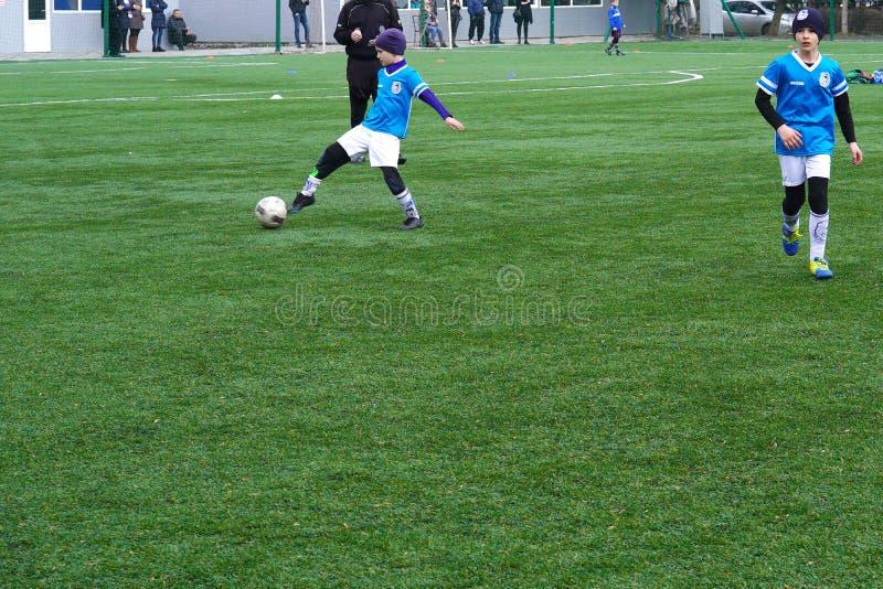 Kind-` s Fußball-Team auf der Neigung Fußballübungsfeld der Kinder Junge Fußball-Spieler, die den Ball nachlaufen stockbilder