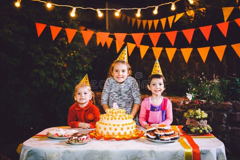 Kind-` s Geburtstagsfeier Drei nette Kindermädchen am Tisch Kuchen mit ihren Händen essend und ihr Gesicht schmierend Spaß a lizenzfreie stockfotografie