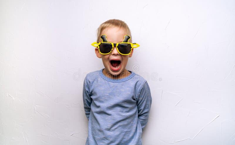 Kind-` s Gefühle und Schreien: Ein kleiner Junge in der lustigen gelben Sonnenbrille schreit gegen die weiße Wand stockbild