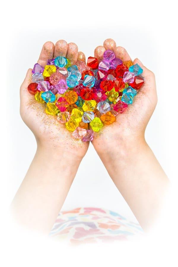 Kind-` s Hände, Hände, die Perlen auf einem weißen Hintergrund halten stockfotos