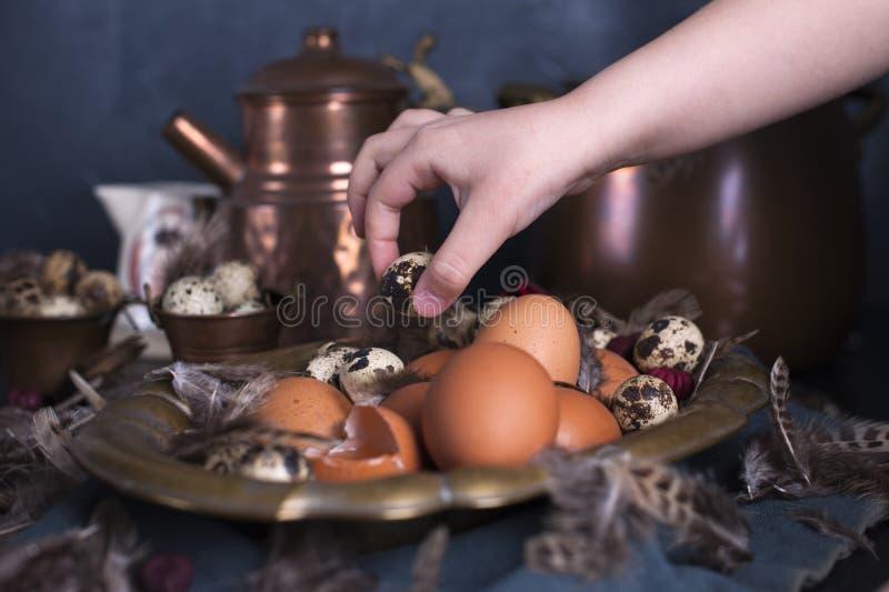Kind-` s Hände im Rahmen, Ostereier groß und klein, Federn Foto in der Weinleseart Ländliches Zubehör Kopieren Sie Platz stockbild