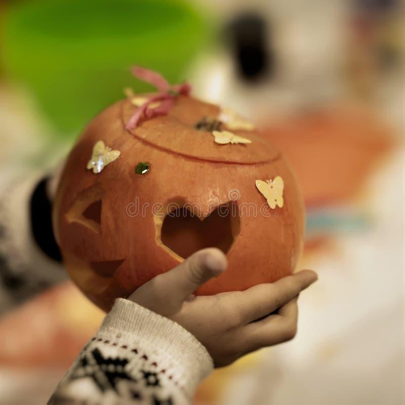 Kind-` s Hände mit dekorativem geschnitztem und verziertem Kürbis Traditionelles Symbol für Erntefeiertage, Danksagungs-Tag stockfotos