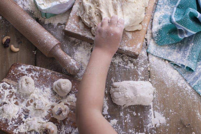 Kind-` s Hände reißen den Teig, das Mehl wird zerstreut auf einen Holztisch und ein grünes Tuch, ein Nudelholz und ein Brett ause lizenzfreie stockbilder
