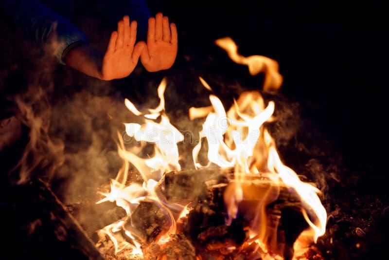 Kind` s handen aan het branden van kampvuur bij nacht worden uitgerekt die Verwarmende palmen bij brand royalty-vrije stock fotografie