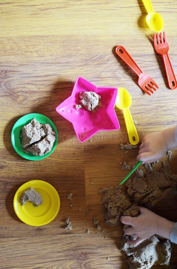 Kind` s handen die met kinetisch zand en kleurrijk plastic speelgoed spelen royalty-vrije stock afbeeldingen