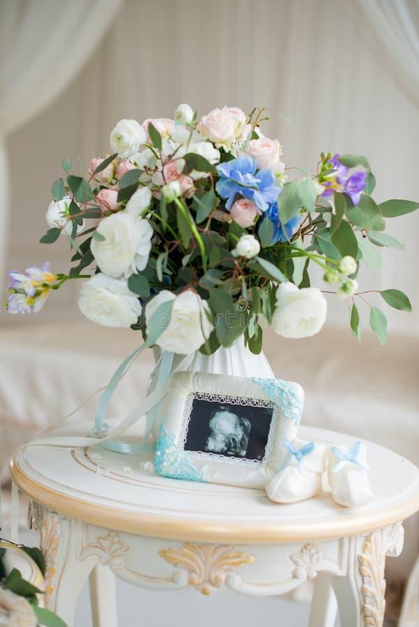 Kind-` s Schuhe und Ultraschall des Baby ` s Fötusses mit einem schönen Blumenstrauß von Blumen lizenzfreie stockbilder