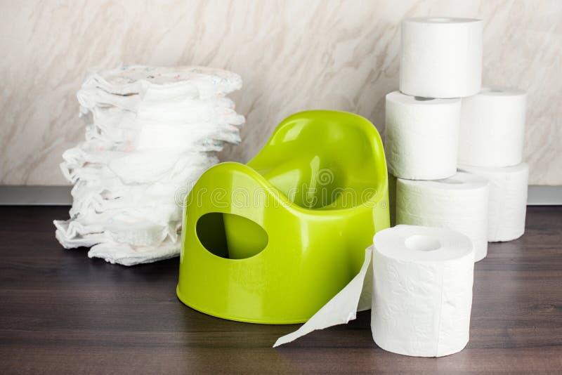 Kind-` s Toiletten-Topfgrün, Windeln und Toilettenpapier, das Konzept des Baby ` s Überganges von den Windeln zur Toilette lizenzfreie stockfotos
