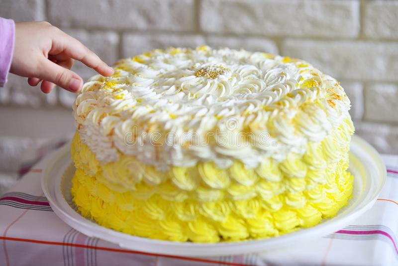 Kind` s vinger op de cake stock foto