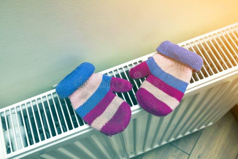 Kind-` s warme handgestrickte gestreifte woolen Handschuhe, die draußen auf Heizungsheizkörper nach Wintertag trocknen lizenzfreies stockbild