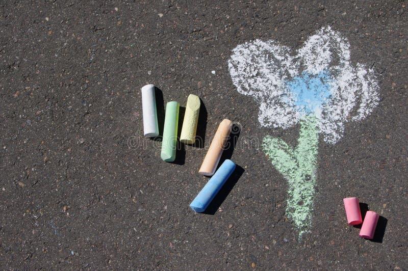 Kind-` s Zeichnung der Blume und der bunten Kreiden auf einer Straße stockfotografie
