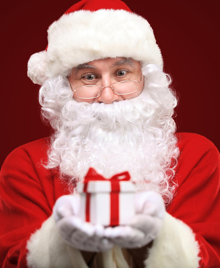Kind Santa Claus giving xmas present. Photo of kind Santa Claus giving xmas present and looking at camera stock photography