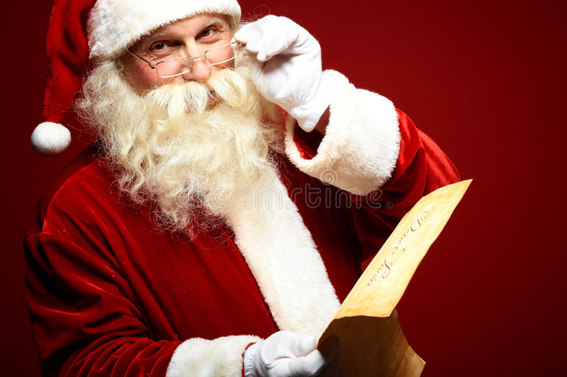 Kind Santa Claus. Portrait of happy Santa Claus holding Christmas letter in his hands and looking at camera royalty free stock image