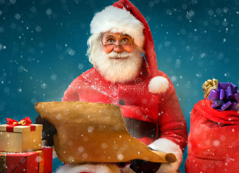 Kind Santa Claus with vintage list and gifts on blue background. Merry Christmas & New Year's Eve concept royalty free stock images