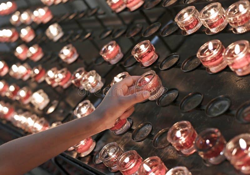 Kind schaltet eine rote Kerze in der Kirche ein und dann sagt er ein Gebet stockfotos