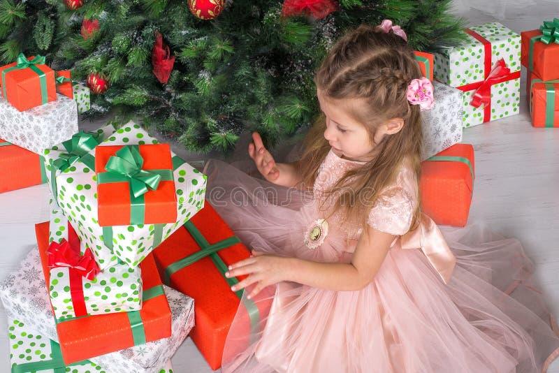 Kind schaut Geschenke unter einem Weihnachtsbaum stockfoto