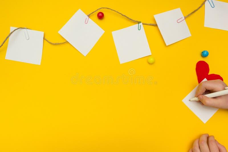 Kind schreibt eine Anmerkung auf ein Blatt Papier auf der Wäscheleine Heller Hintergrund stockfotografie