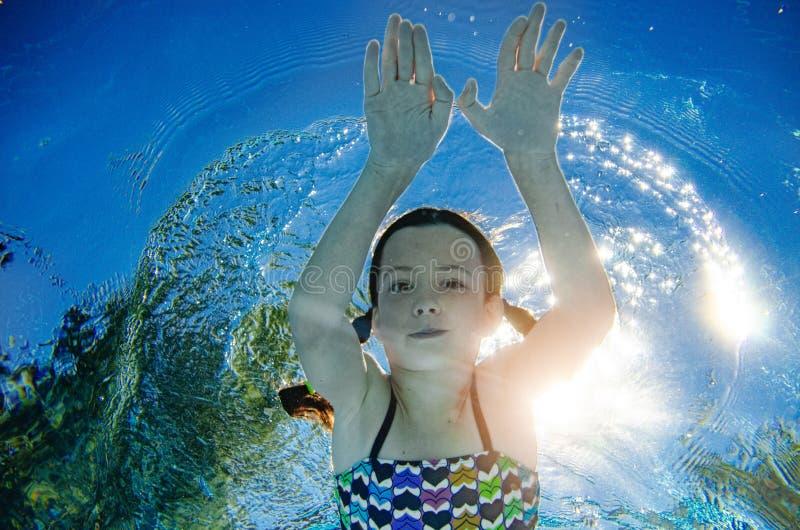 Kind schwimmt unter Wasser im Swimmingpool, gl?ckliches aktives Jugendlichm?dchentauchen und hat Spa? unter Wasser, Kindereignung lizenzfreies stockbild