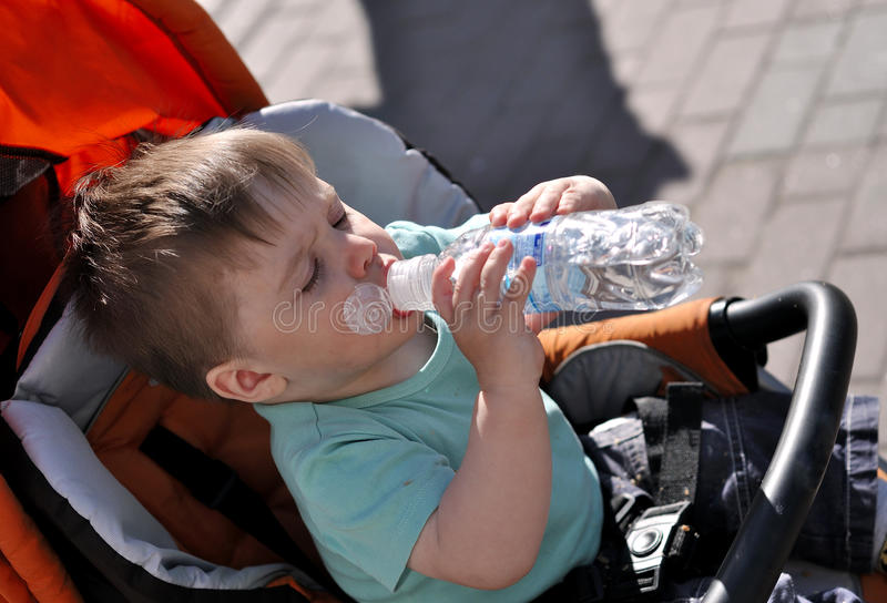 Kind selbst trinkt Wasser von einer Flasche in einem stoller lizenzfreie stockfotografie