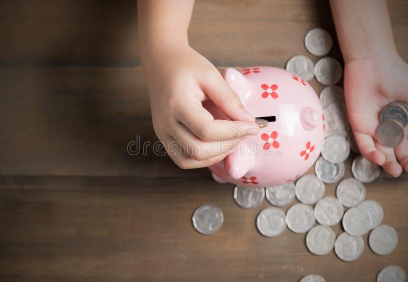 Kind setzte Münze zum Sparschwein auf dem Weinleseholzhintergrund stockbilder
