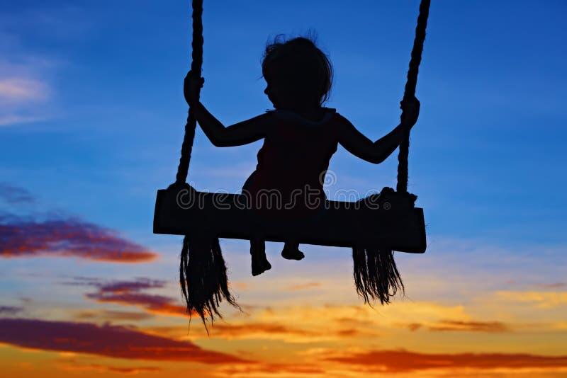 Kind sitzen auf Schwingen auf buntem Sonnenunterganghimmelhintergrund lizenzfreie stockfotografie
