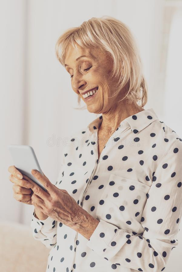 Cheerful woman being high spirited. Kind smile. Delighted female person expressing positivity while staring at her gadget stock photo
