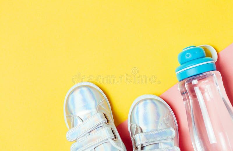 Kind-sneackers und Flasche Wasser auf gelbem Hintergrund lizenzfreies stockbild