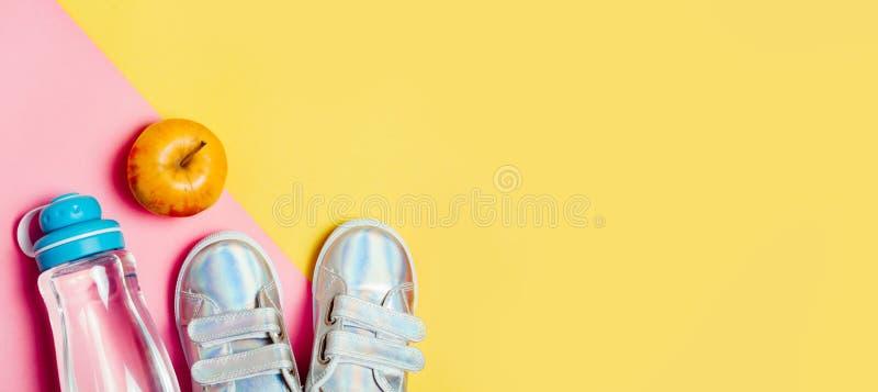 Kind-sneackers und Flasche Wasser auf gelbem Hintergrund stockfoto