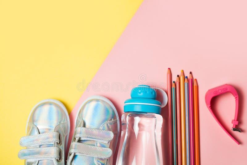 Kind-sneackers und Flasche Wasser auf gelbem Hintergrund lizenzfreies stockfoto