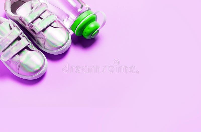 Kind-sneackers und Flasche Wasser auf Rosa- und weißemhintergrund lizenzfreies stockfoto