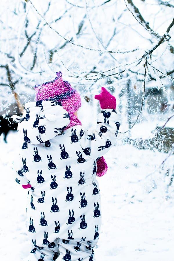 Kind in sneeuwdag Babymeisje in witte snowsuite en roze hoed, laarzenhandschoenen in het park van de sneeuwwinter stock foto's