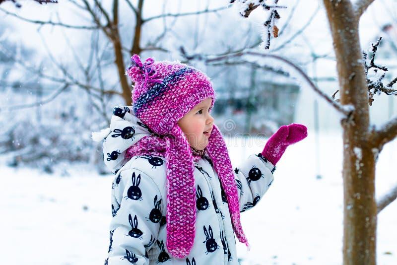 Kind in sneeuwdag Babymeisje in witte snowsuite en roze hoed, laarzenhandschoenen in het park van de sneeuwwinter royalty-vrije stock fotografie