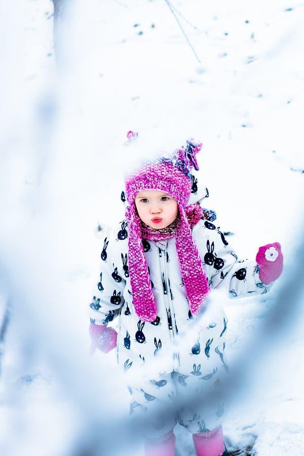 Kind in sneeuwdag Babymeisje in witte snowsuite en roze hoed, laarzenhandschoenen in het park van de sneeuwwinter stock foto