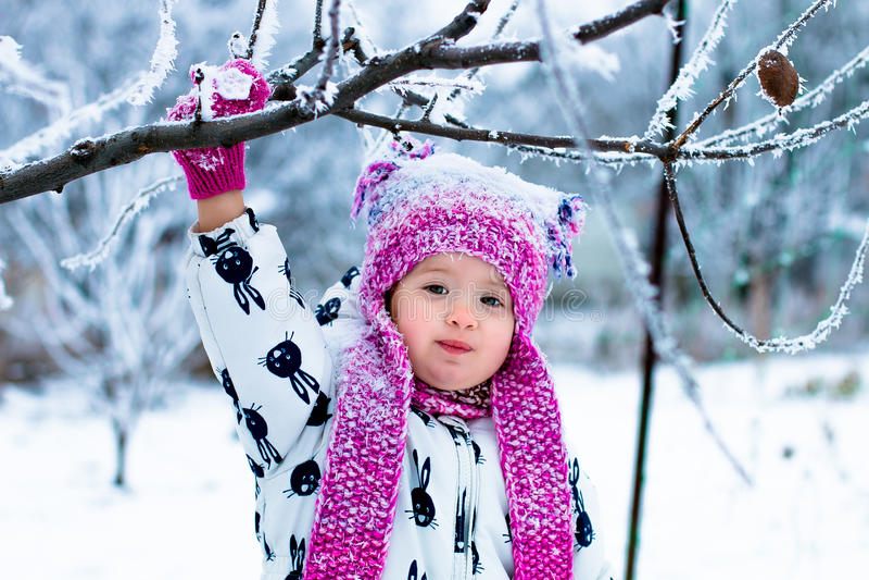 Kind in sneeuwdag Babymeisje in witte snowsuite en roze hoed, laarzenhandschoenen in het park van de sneeuwwinter gelukkig royalty-vrije stock foto
