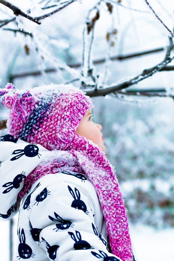 Kind in sneeuwdag Babymeisje in witte snowsuite en roze hoed, laarzenhandschoenen in het park van de sneeuwwinter gelukkig royalty-vrije stock afbeelding