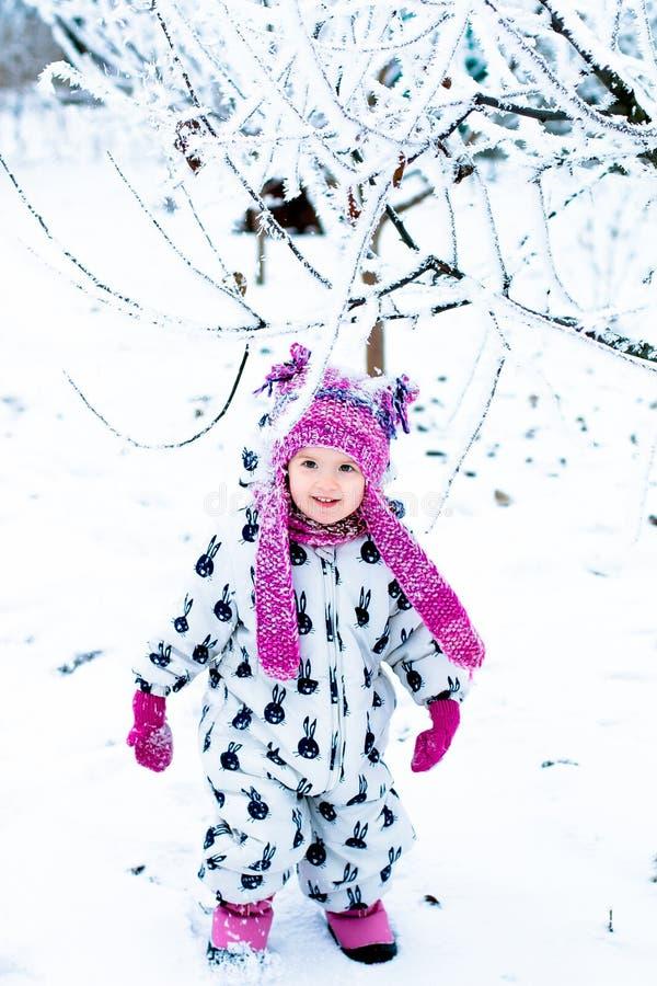 Kind in sneeuwdag Babymeisje in witte snowsuite en roze hoed, laarzenhandschoenen in het park van de sneeuwwinter gelukkig stock foto