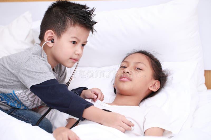 Kind speelarts of verpleegster met pluchemeisje met helder op stock fotografie