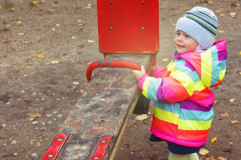 Kind spielt auf Spielplatz mit Schwingen Kleines kaukasisches Mädchen im Herbst im Park stockbild