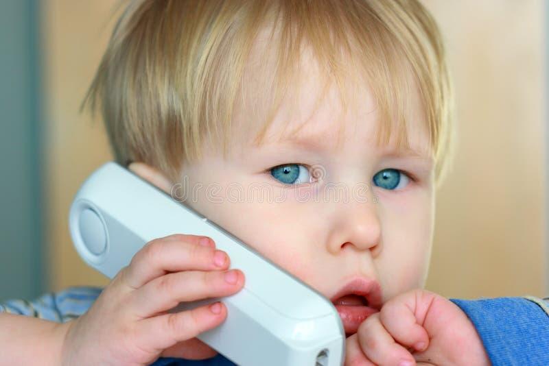 Kind spricht durch Telefon lizenzfreie stockfotos