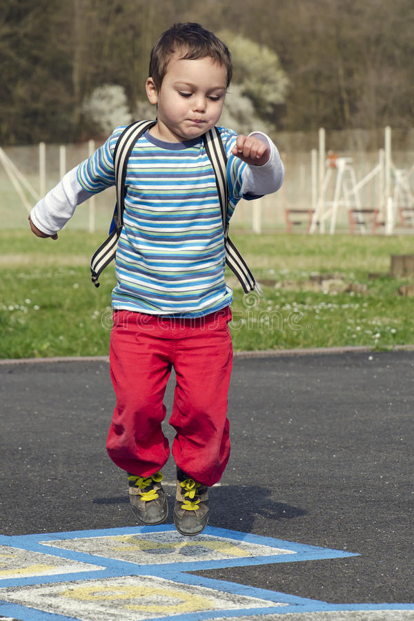 Kind springende hinkelspels stock afbeeldingen
