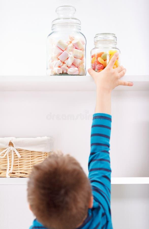 Kind stealing suikergoed van de plank stock foto