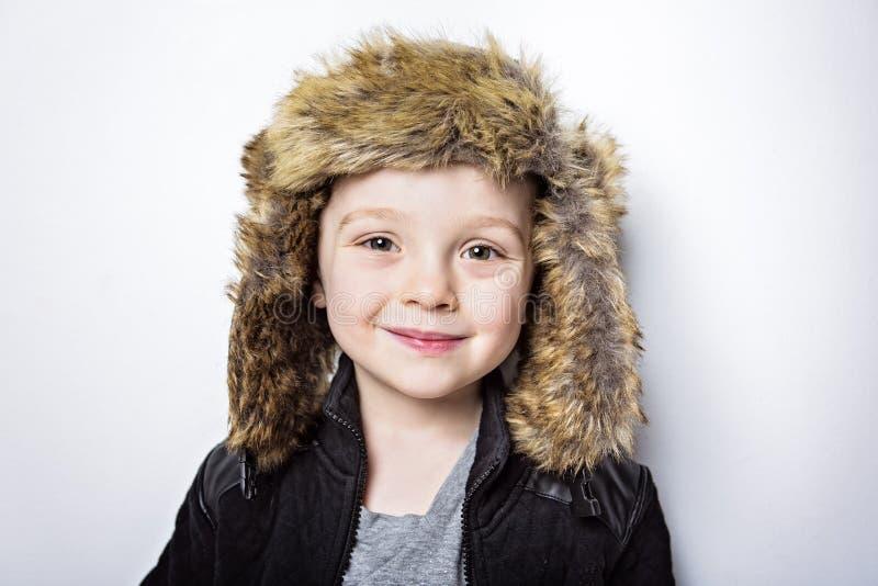Kind in stijl van de de manier de toevallige winter van de bonthoed weinig jongen stock foto's