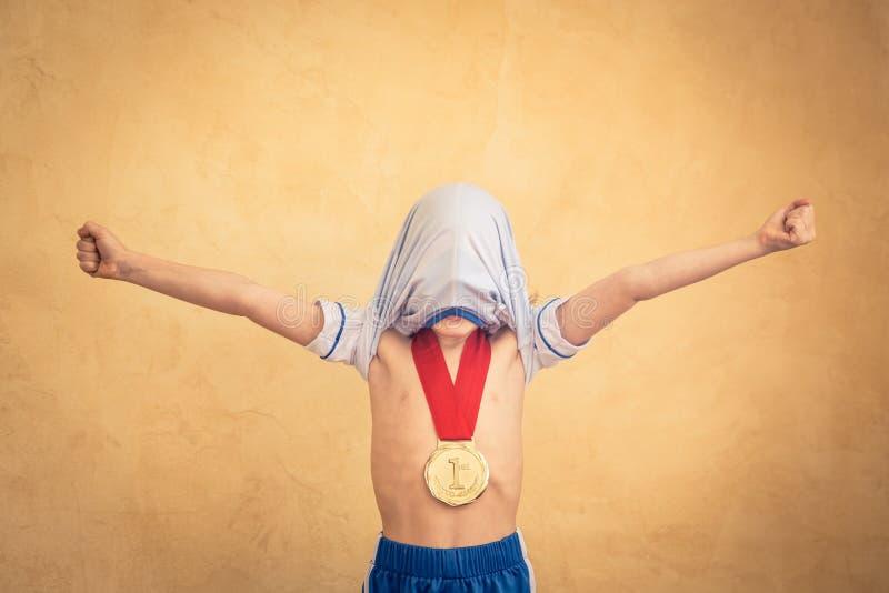 Kind täuscht vor, ein Fußballspieler zu sein lizenzfreie stockfotografie