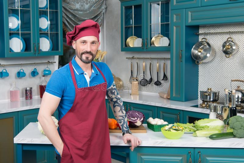 Kind tattooed chef in red apron and red cap standing on kitchen. Smiling tattooed chef in red apron and red cap standing on kitchen lean on table. Guy prepared royalty free stock images