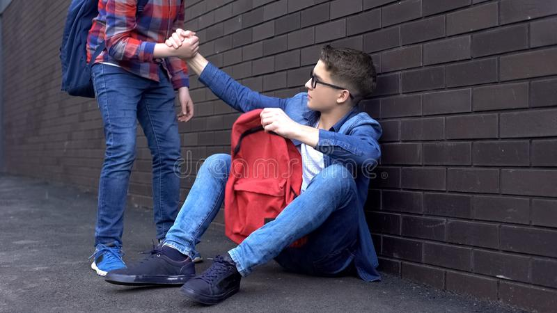 Kind teenage student giving helping hand to bullied nerd boy, supportive friend. Stock photo stock image